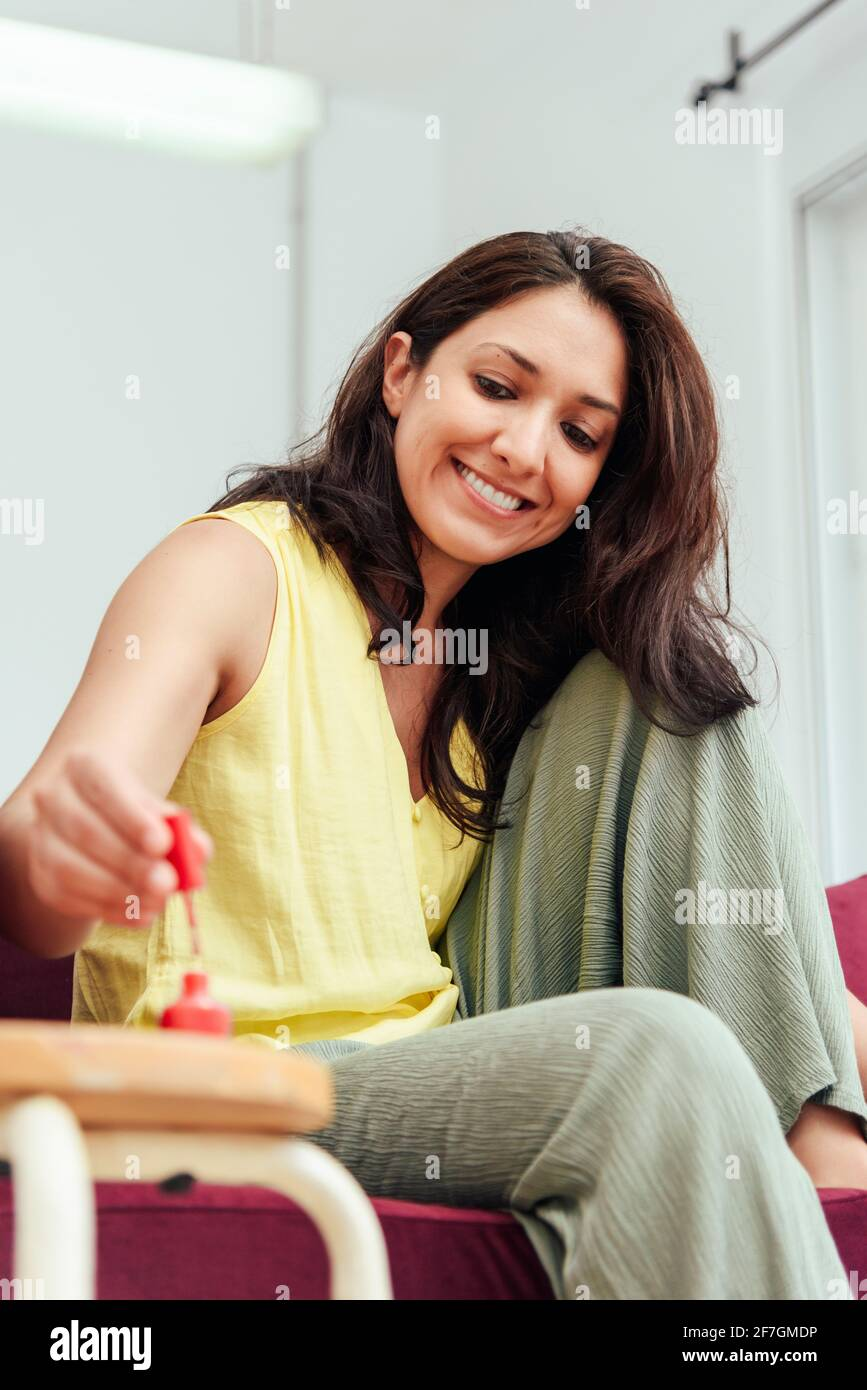 Happy adult woman smiling and applying nail polish on toenails while sitting on sofa on weekend day at home Stock Photo