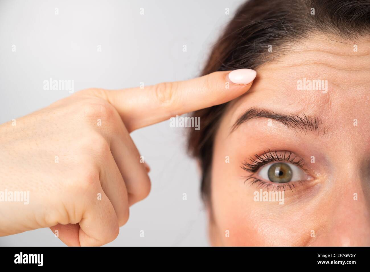 Close-up portrait of Caucasian middle-aged woman showing wrinkles on her forehead. Signs of aging on the face Stock Photo