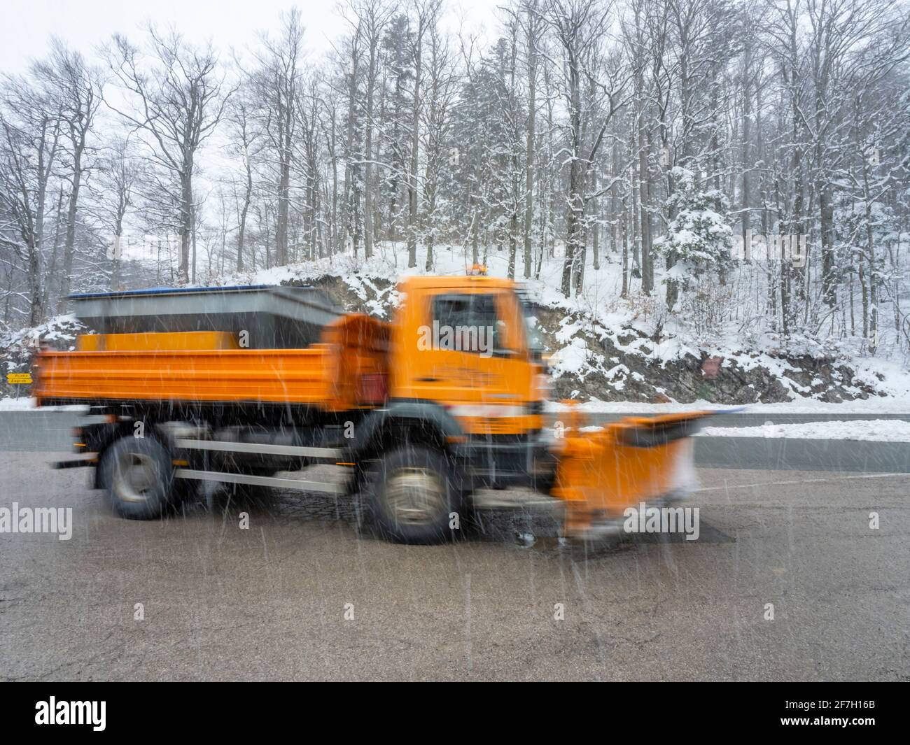 Snow falling road cleaning preparation snowplowing truck passing by going to work intentionally blurry longish exposure Stock Photo