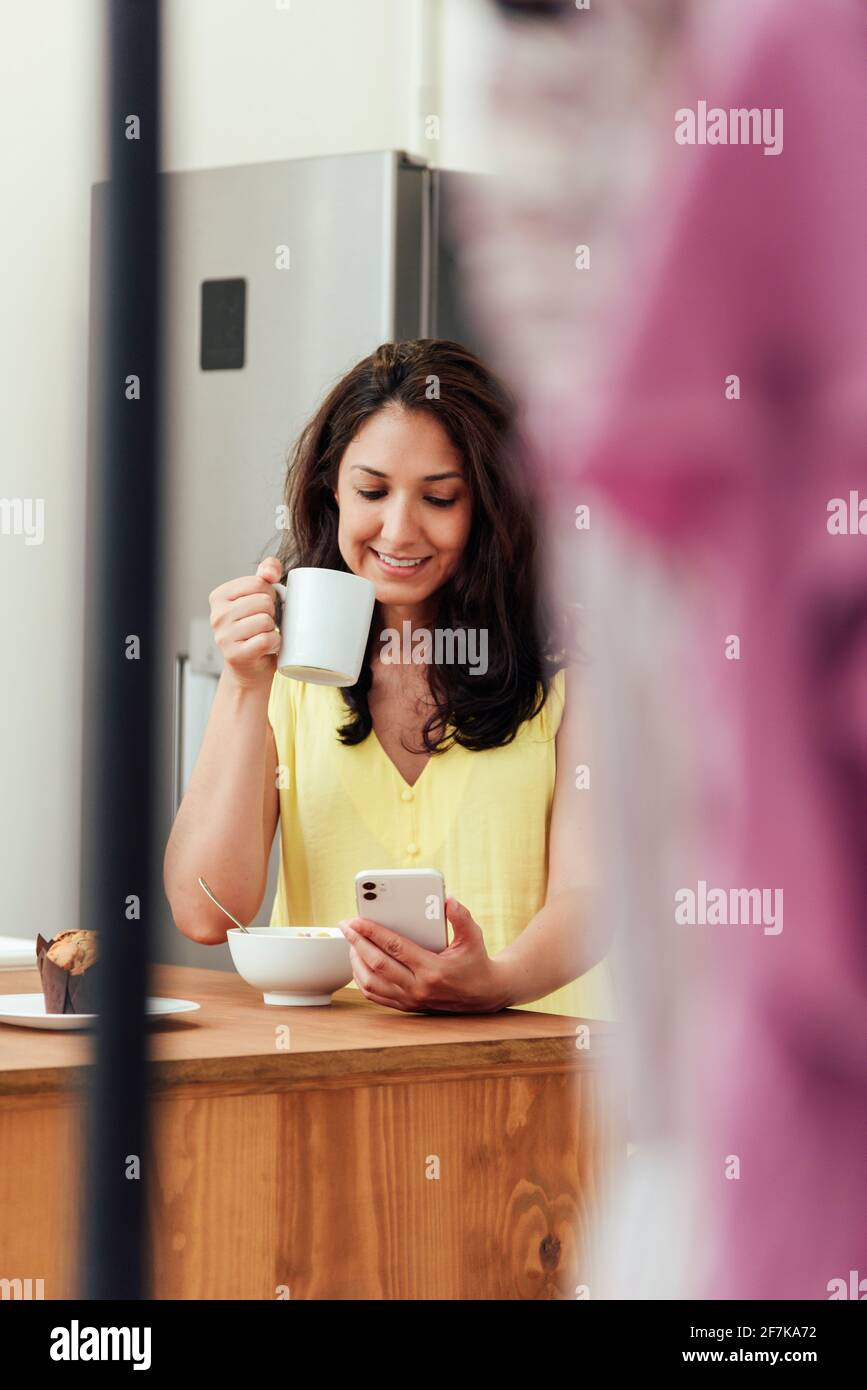 Woman talking on the phone while having breakfast in the kitchen at home Stock Photo
