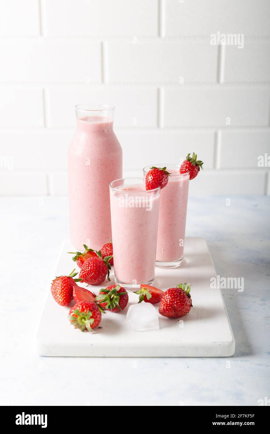 Fresh homemade cold strawberry smoothie with ice cubes and fresh strawberries on white background. Stock Photo
