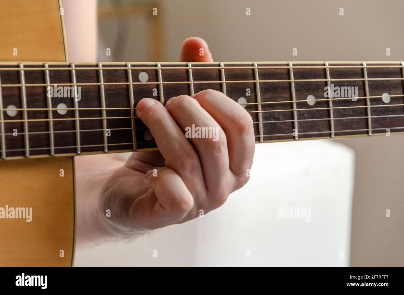 closeup on male fingers playing acoustics arm guitar strings Stock Photo