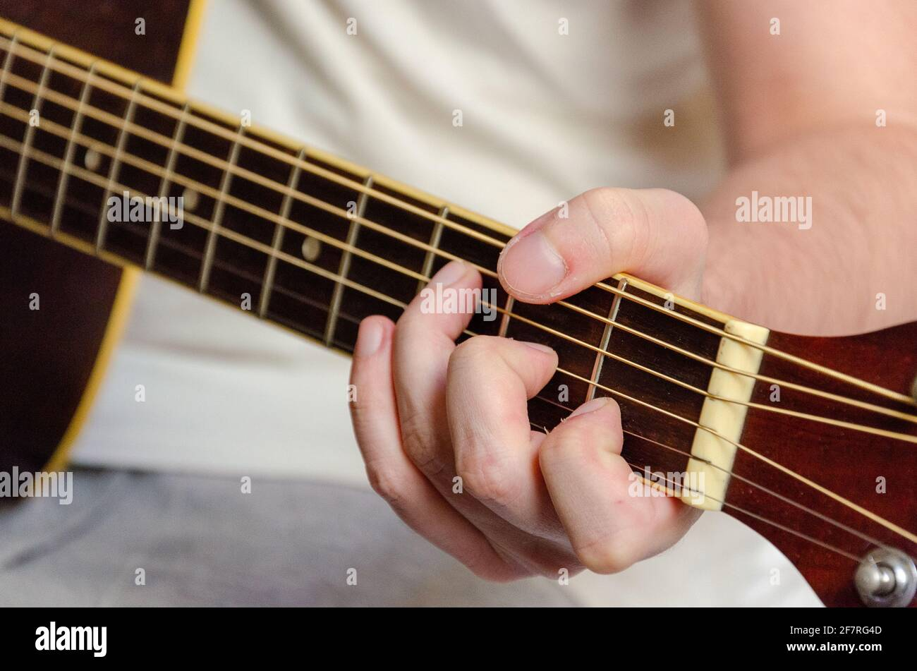 male fingers playing acoustics guitar strings Stock Photo
