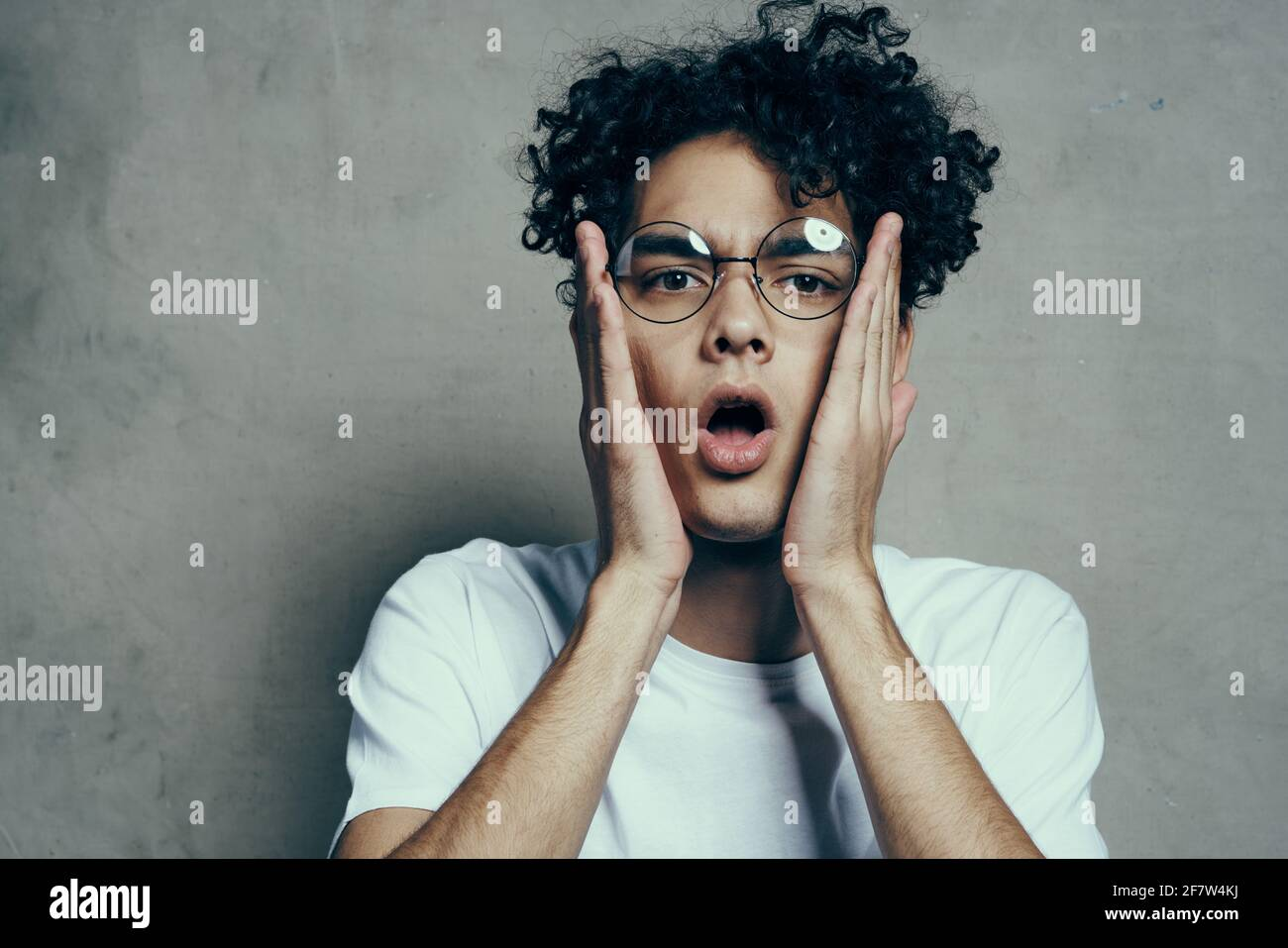 guy with curly hair emotions glasses fashion studio close-up Stock Photo