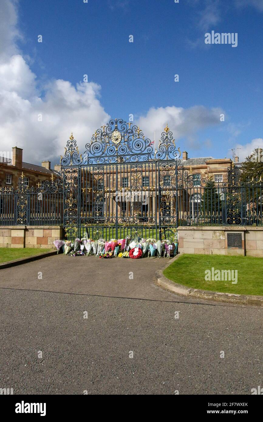 Hillsborough Castle, Hillsborough, County Down, Northern Ireland, UK. 10 April 2021. With the Union flag at half-mast, floral tributes have been left outside the gates of HM The Queen's official residence in Northern Ireland as the public mourn the loss of Prince Philip, Duke of Edinburgh, who died yesterday. Credit: David Hunter/Alamy Live News. Stock Photo