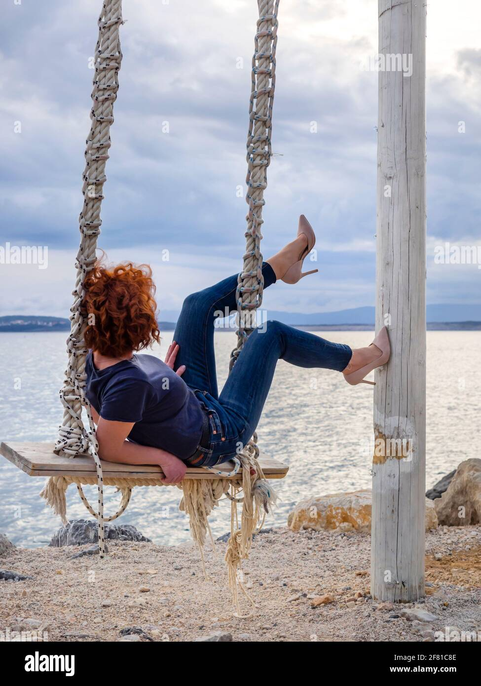 Woman redhair redhaired Red hair curls curly playful playground on swings on seaside legs heels Stock Photo