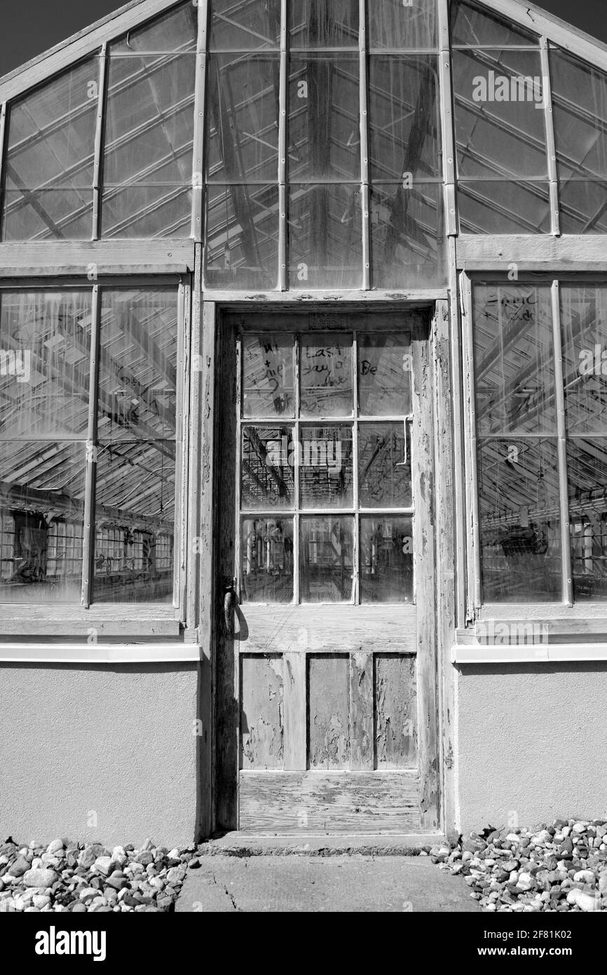 Black & white shot of a very worn front door of an empty greenhouse at the Central Experimental Farm, Ottawa, Ontario, Canada. Stock Photo