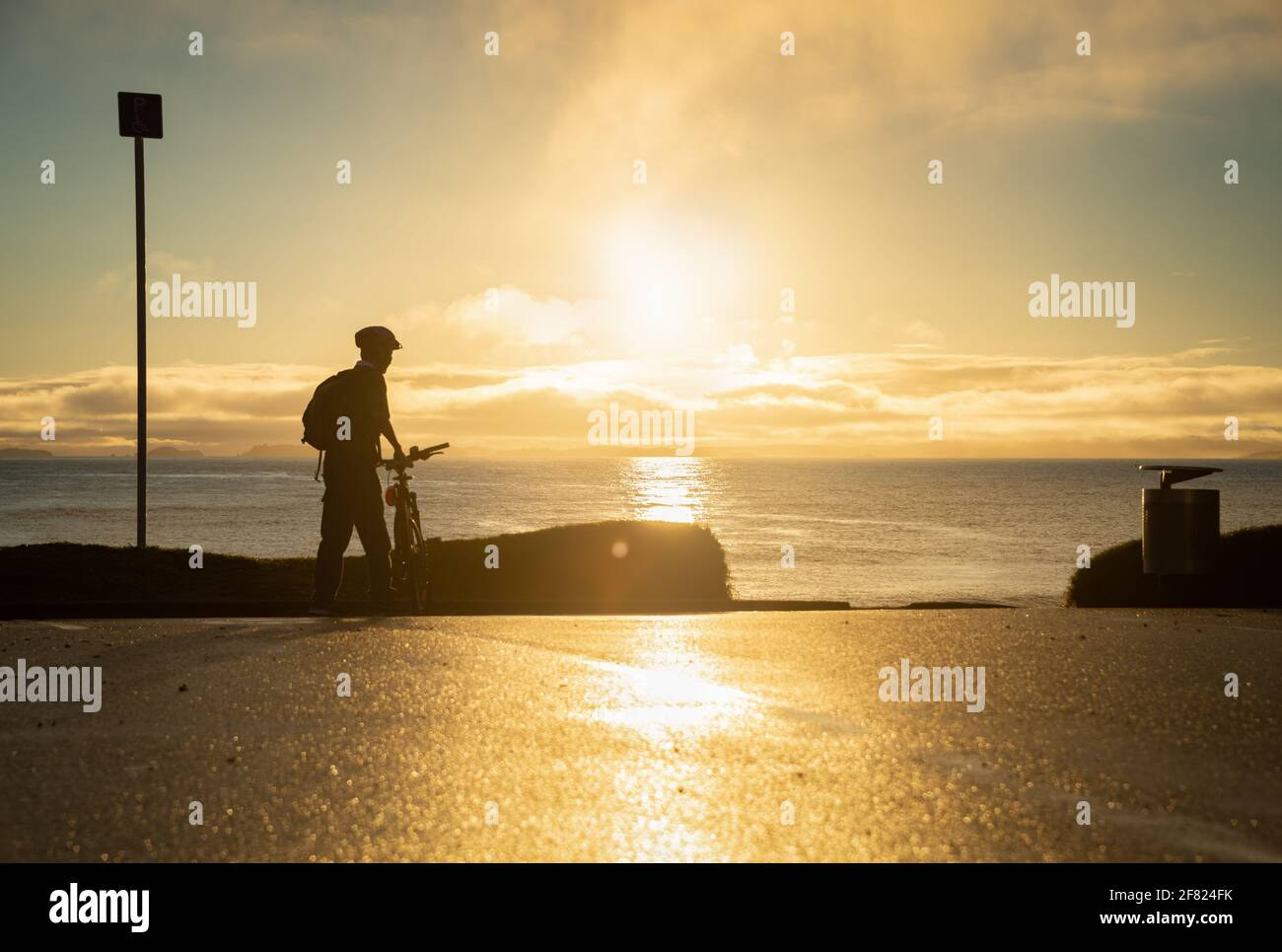 Silhouette image of a cyclist getting ready to ride on the beach at sunrise Stock Photo