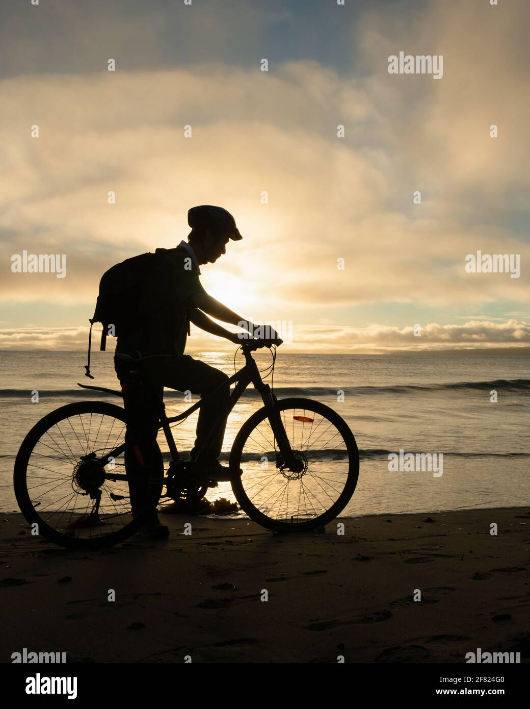 Silhouette image of a cyclist getting ready to ride on the beach at sunrise. Vertical format. Stock Photo