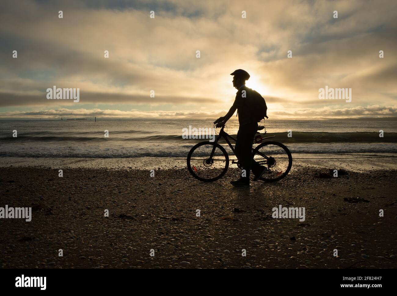 Silhouette image of a cyclist walking and pushing the bike on the beach at sunrise Stock Photo