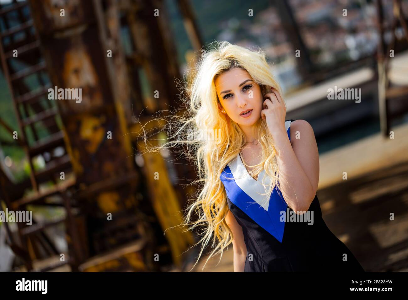 Blonde young woman flying long wavy hair windy blowing wind standing walking walk towards at camera serious industrial industry crane metal framework Stock Photo