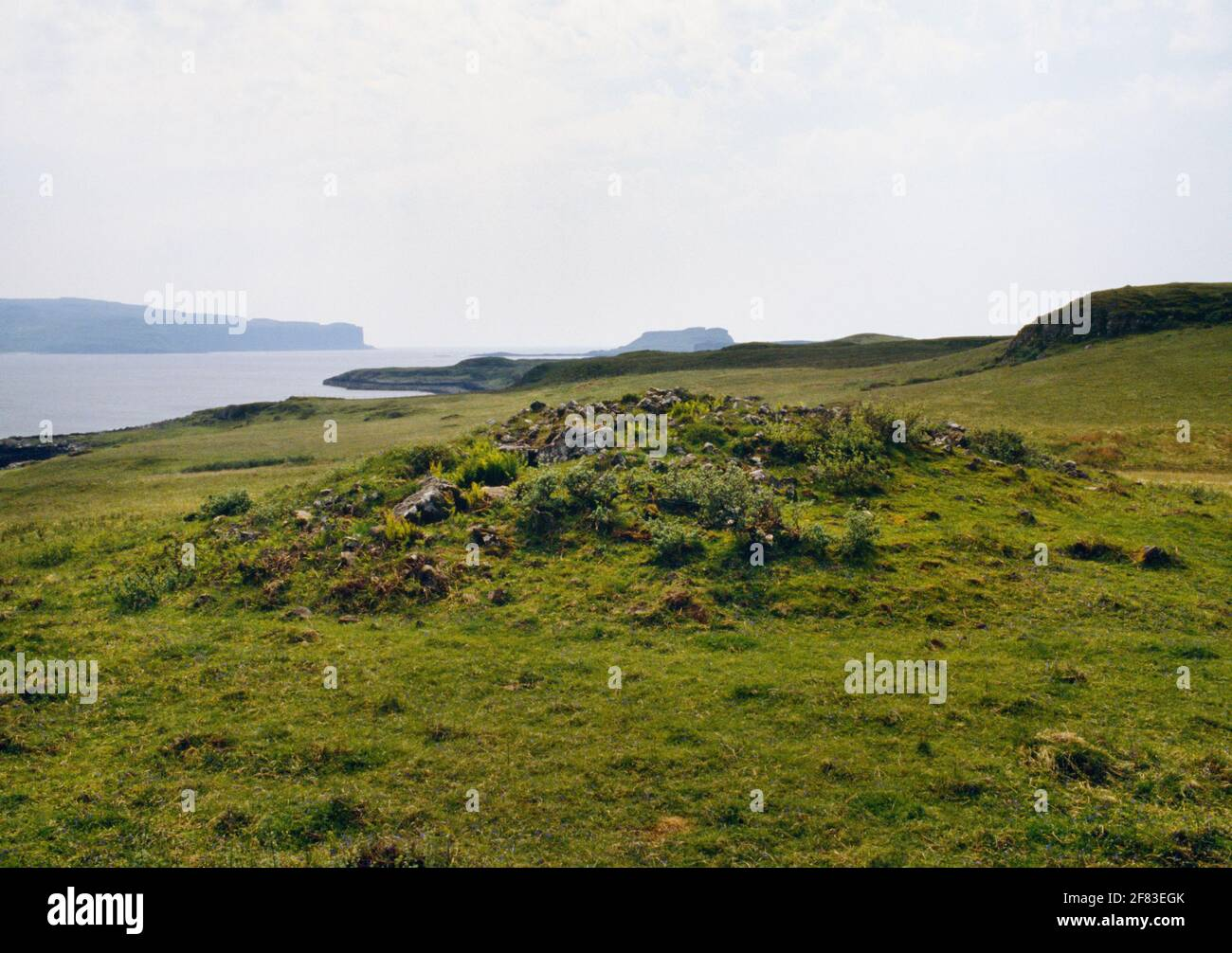 View SW of the remains of Struanmore Neolithic chambered tomb, Bracadale, Isle of Skye, Scotland, UK: Ardtreck Point rear L & Oronsay island rear R. Stock Photo