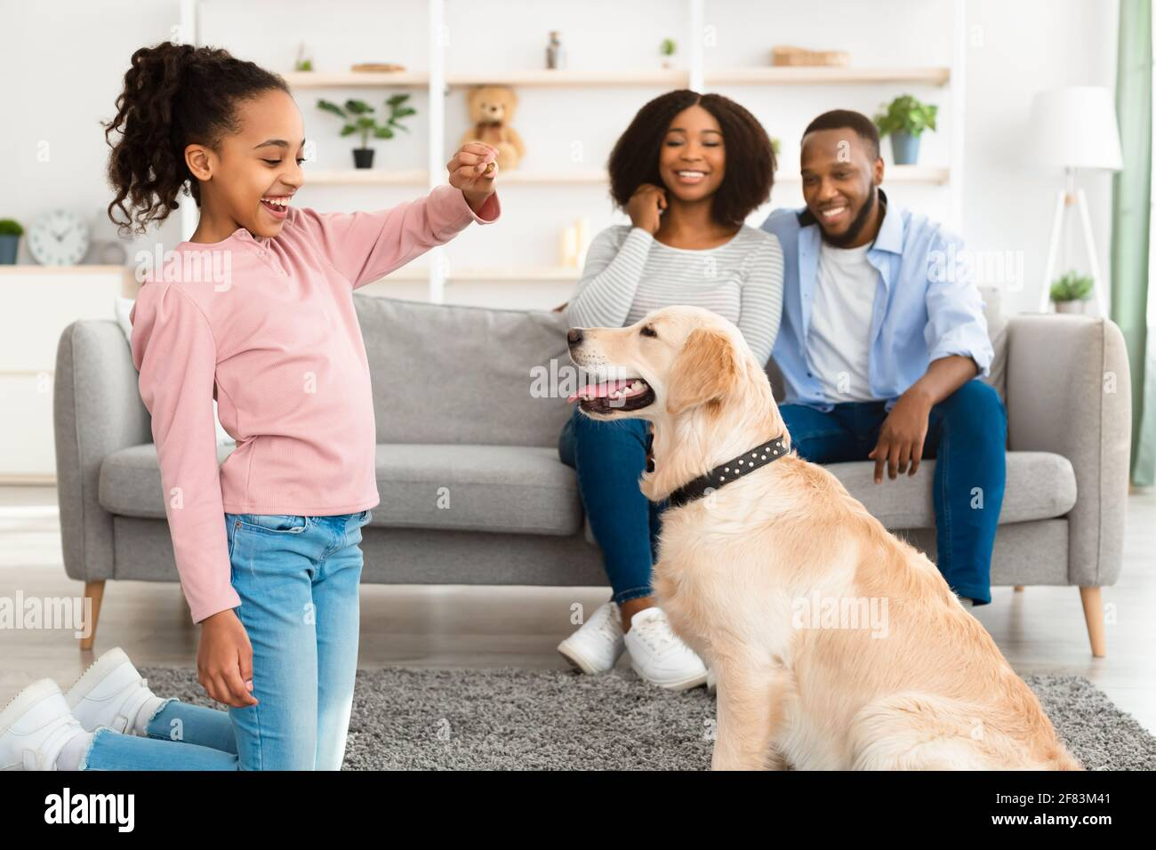 Black girl giving a treat to her obedient dog Stock Photo
