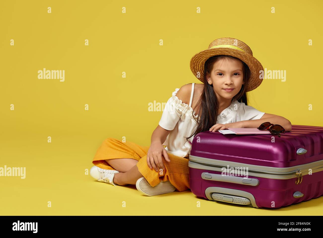 little girl with suitcase and passport sitting on floor Stock Photo