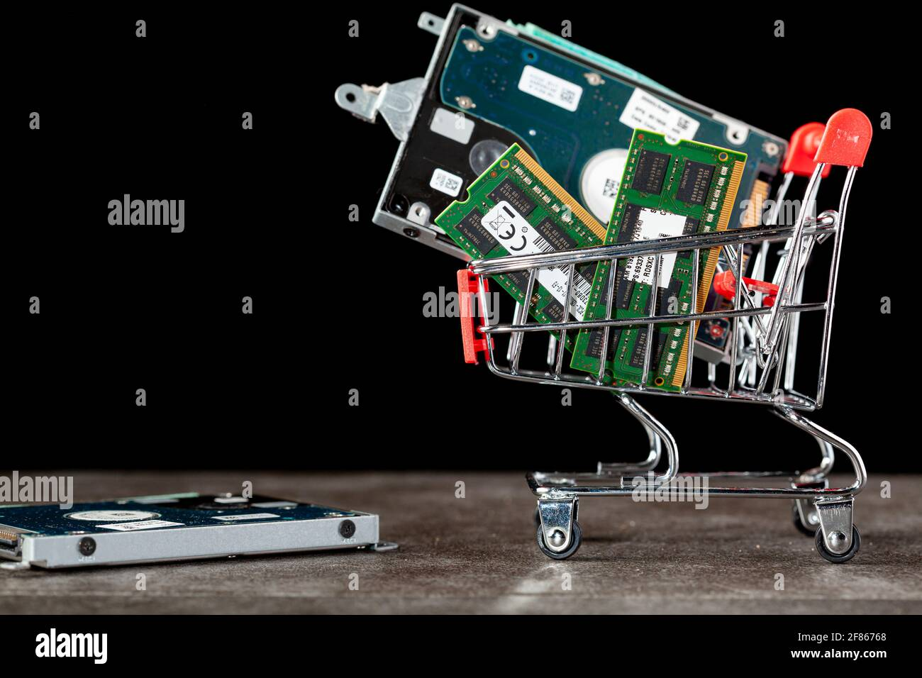 A concept image with a small shopping cart filled with computer parts including RAM memory cards and a hard drive. Shopping for technology, consumer e Stock Photo