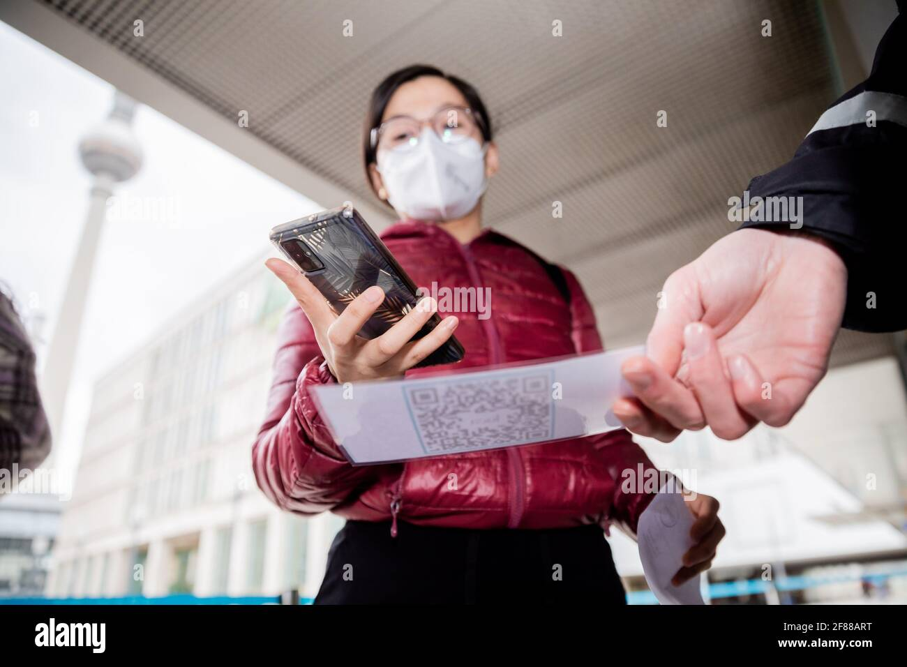 Berlin, Germany. 12th Apr, 2021. A customer scans a QR code at the entrance of a clothing store at Alexanderplatz in front of a security guard using the Luca app. The app is used to provide data for possible contact tracing. Credit: Christoph Soeder/dpa/Alamy Live News Stock Photo