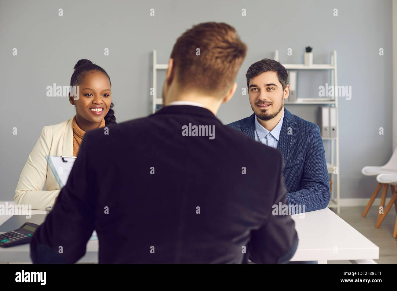 Happy young couple talking to bank manager, insurance advisor or mortgage broker Stock Photo