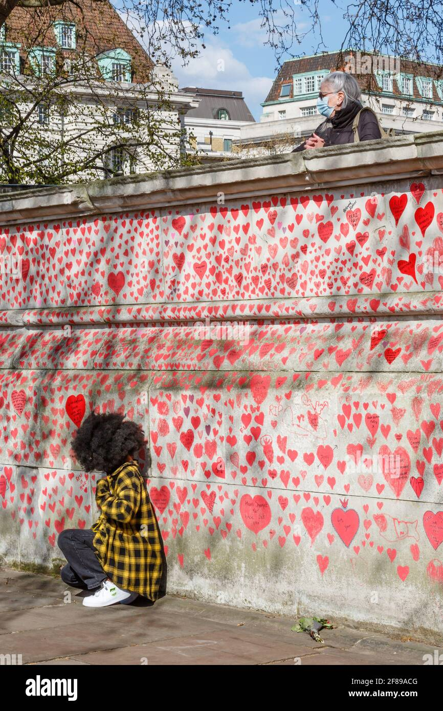 Red hearts painted on the National Covid Memorial Wall as a tribute to the British victims of the Coronavirus pandemic . Stock Photo