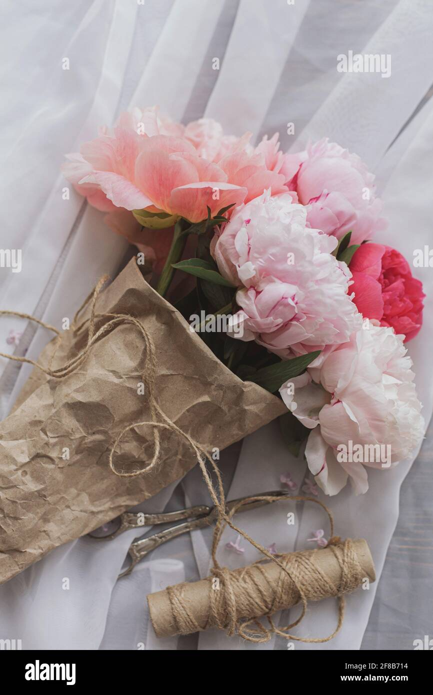 Beautiful stylish peony bouquet in paper, twine, scissors on soft fabric on dark wooden background, top view. Happy Mothers day. Pink and white peonie Stock Photo