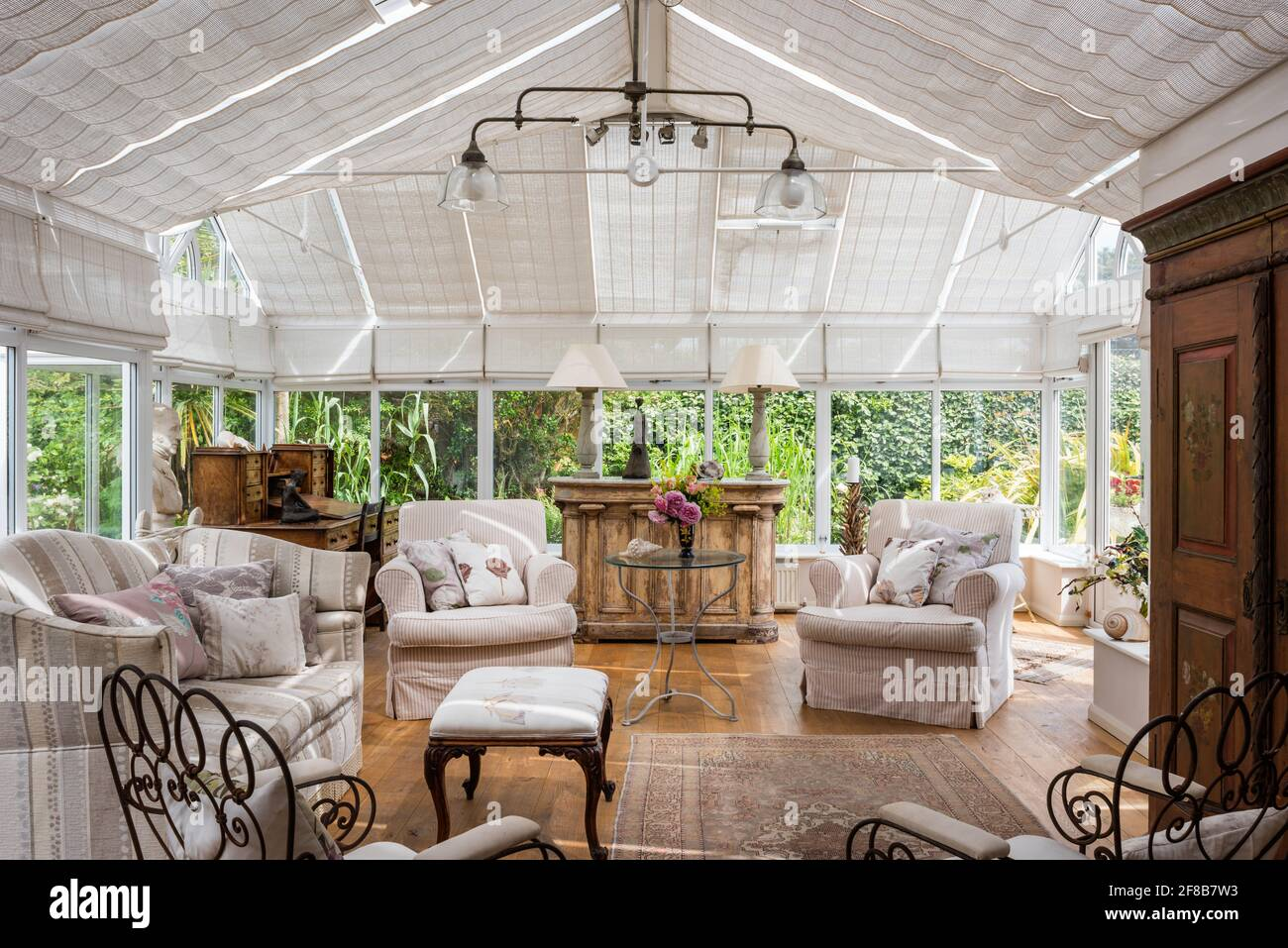 Pair of armchairs and sofa in conservatory extension of 1930s West Sussex coastal home Stock Photo
