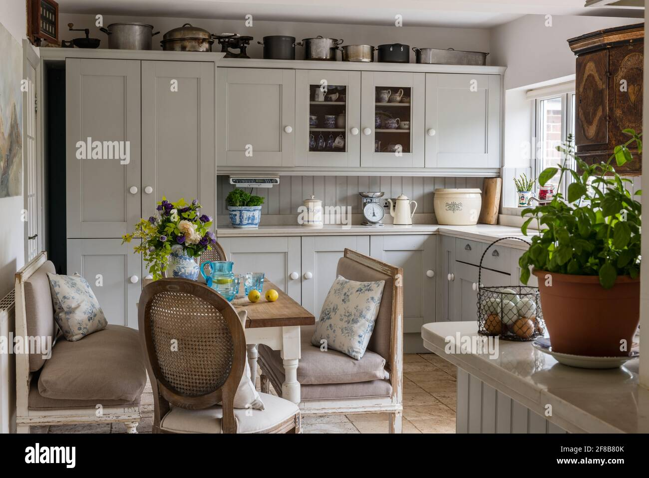 Shaker style kitchen with Gustavian benches in 1930s West Sussex coastal renovation. Stock Photo