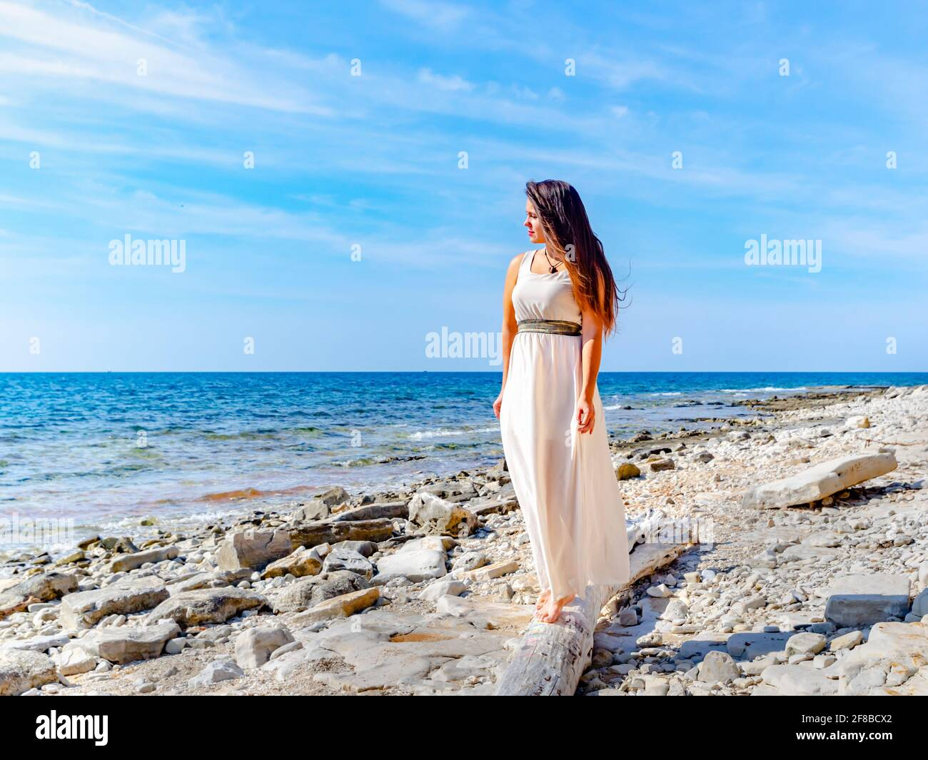 Young woman in White clothing long dress walking barefeet near sea on beach seaside alone lonesome watching looking aside away at distance serious Stock Photo
