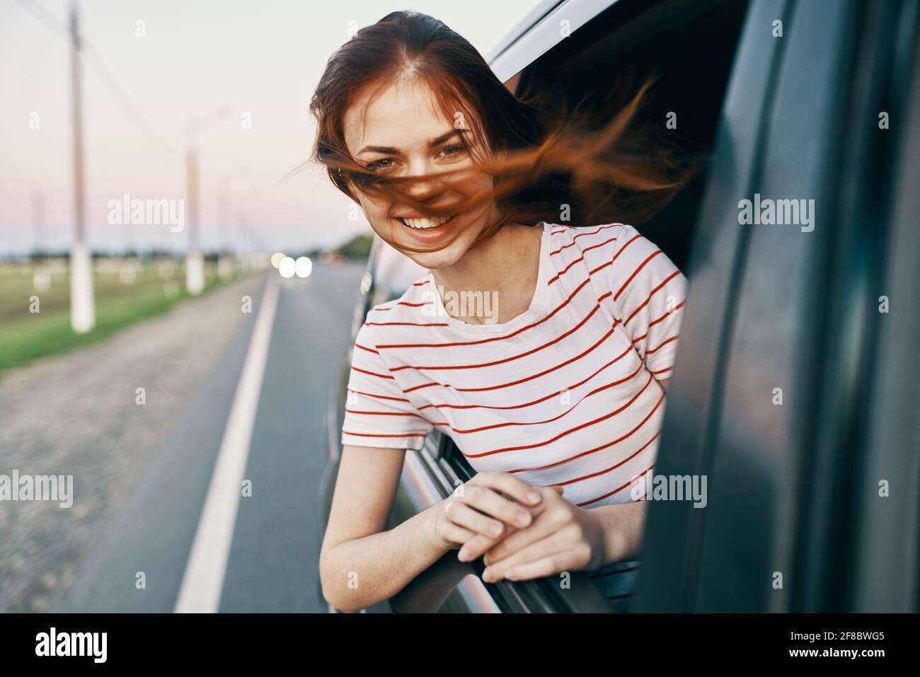 woman in striped t-shirt red hair car window salon model Stock Photo