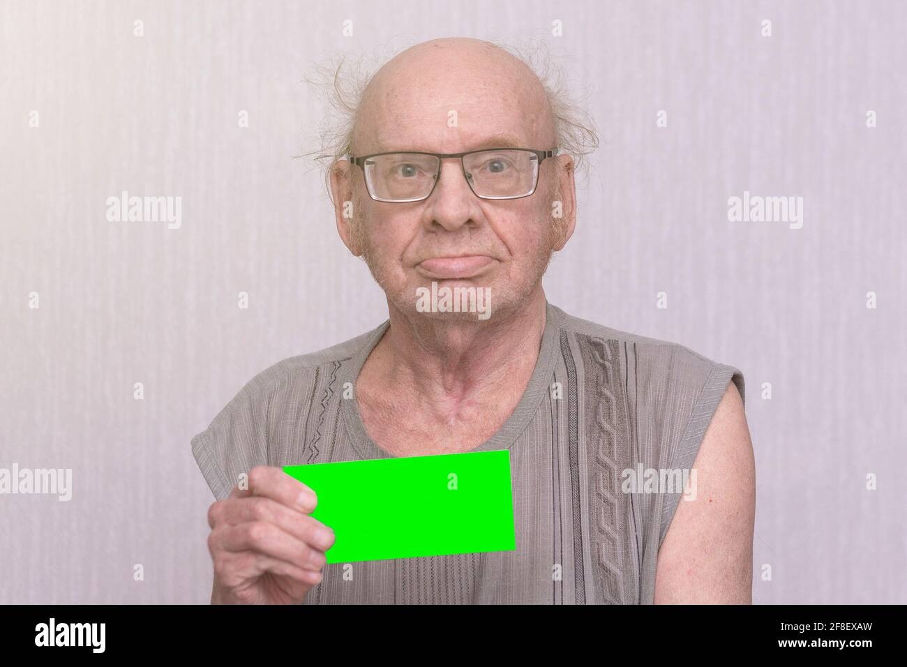Old retired bald man with eyeglasses in gray shirt is blank in his hand. Stock Photo