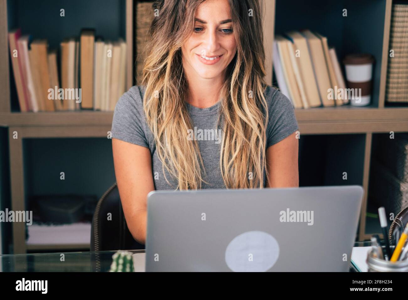 Young businesswoman write on laptop computer at home in smart working office job work activity - remote worker lifestyle concept with pretty female pe Stock Photo