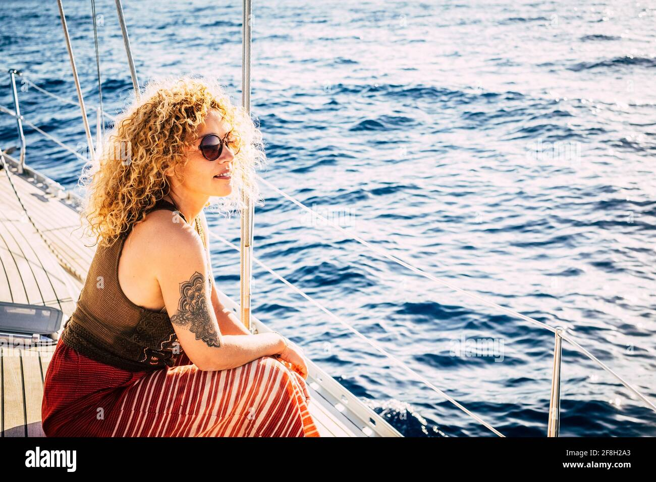 Cheerful attractive young adult blonde woman smile and enjoy the excursion trip sitting on the sail boat deck looking the blue sea around - concept of Stock Photo