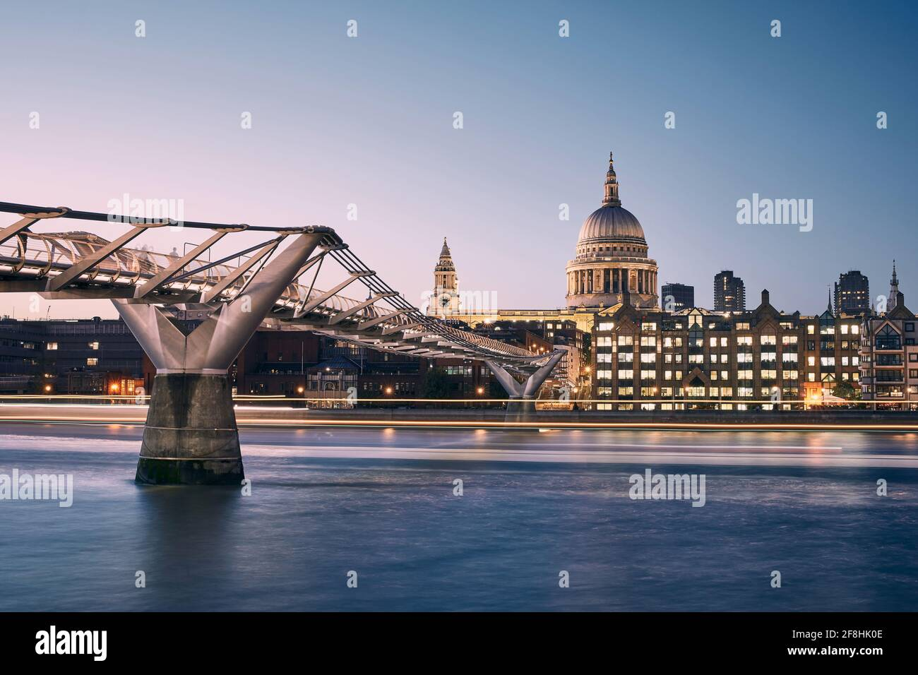 London cityscape at dusk. City waterfront with Millennium Footbridge against St. Pauls Cathedral. United Kingdom. Stock Photo