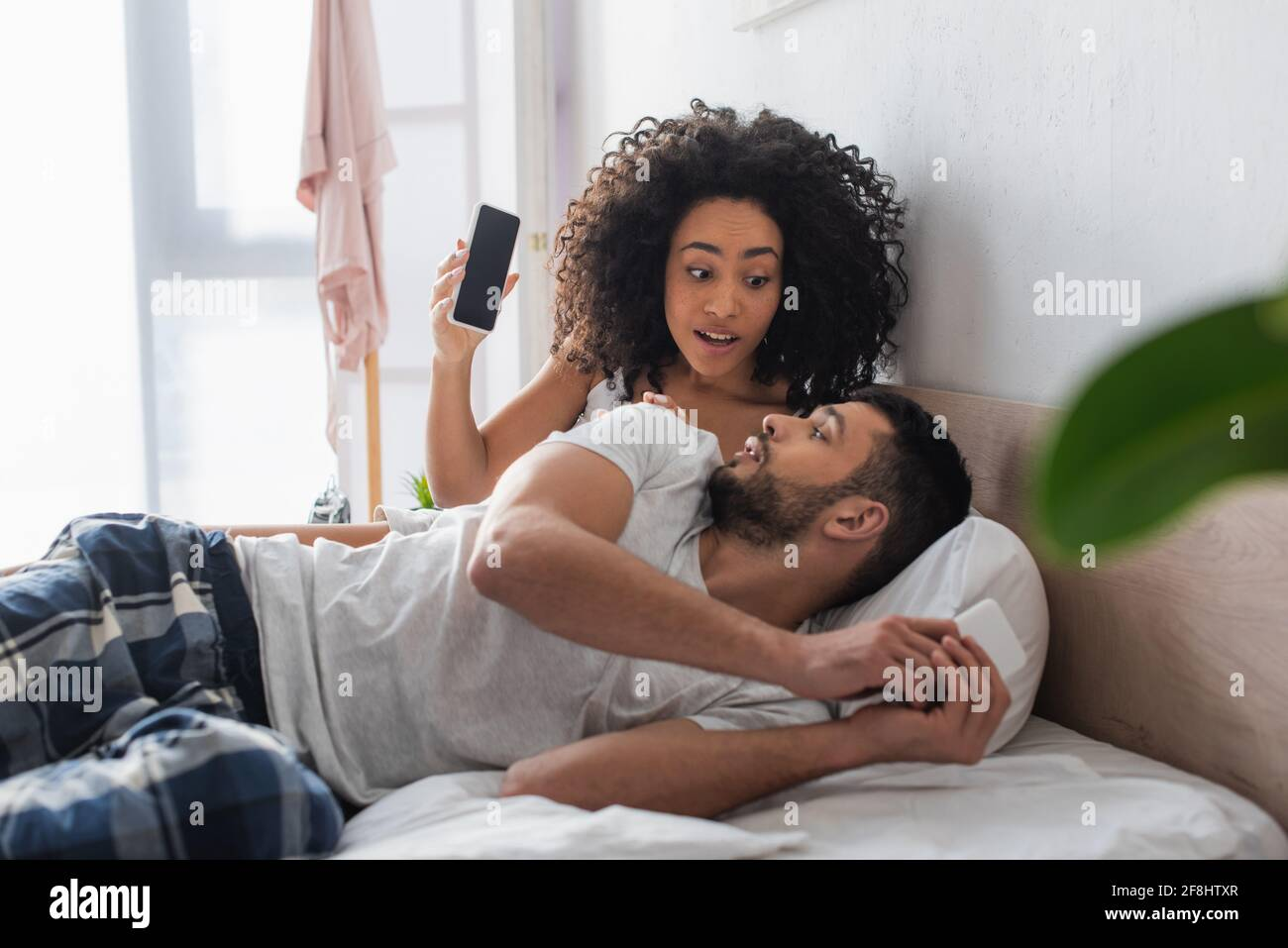 surprised african american woman looking at boyfriend while holding smartphone with blank screen in bedroom Stock Photo