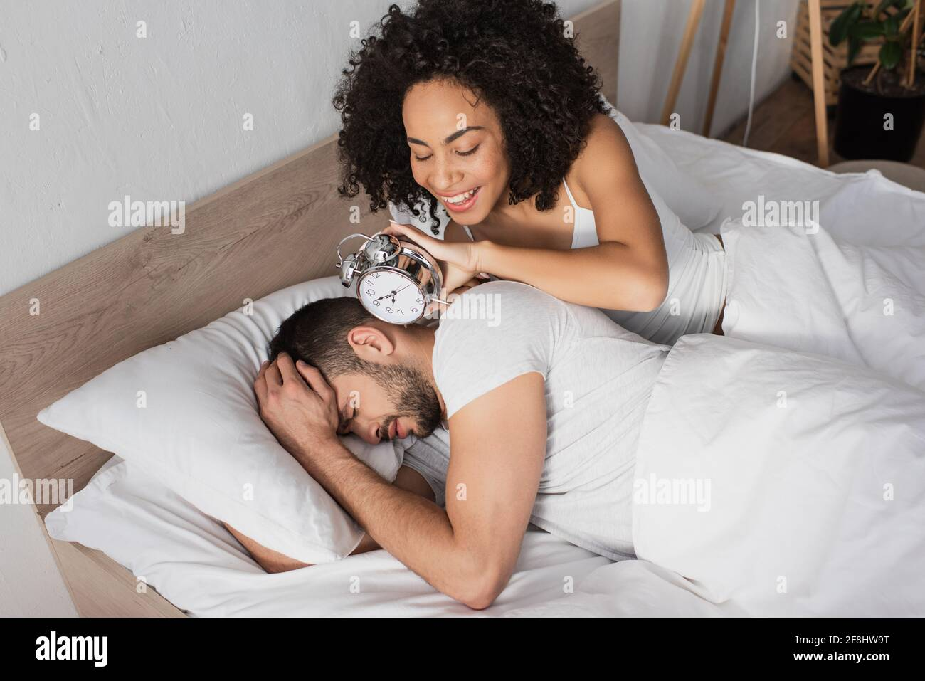 happy african american woman holding alarm clock near displeased man sleeping on bed Stock Photo