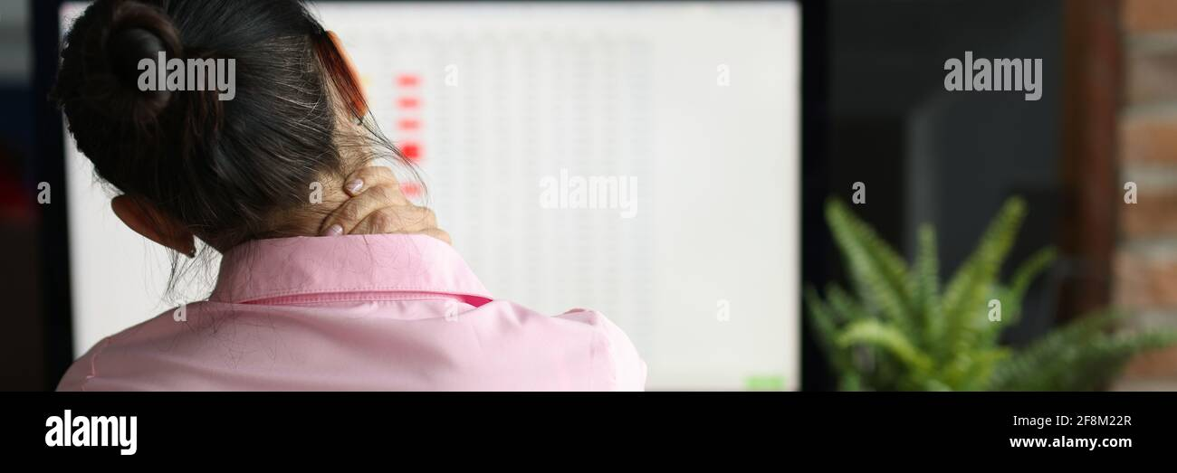 Tired woman sits at computer and massages pain in her neck Stock Photo