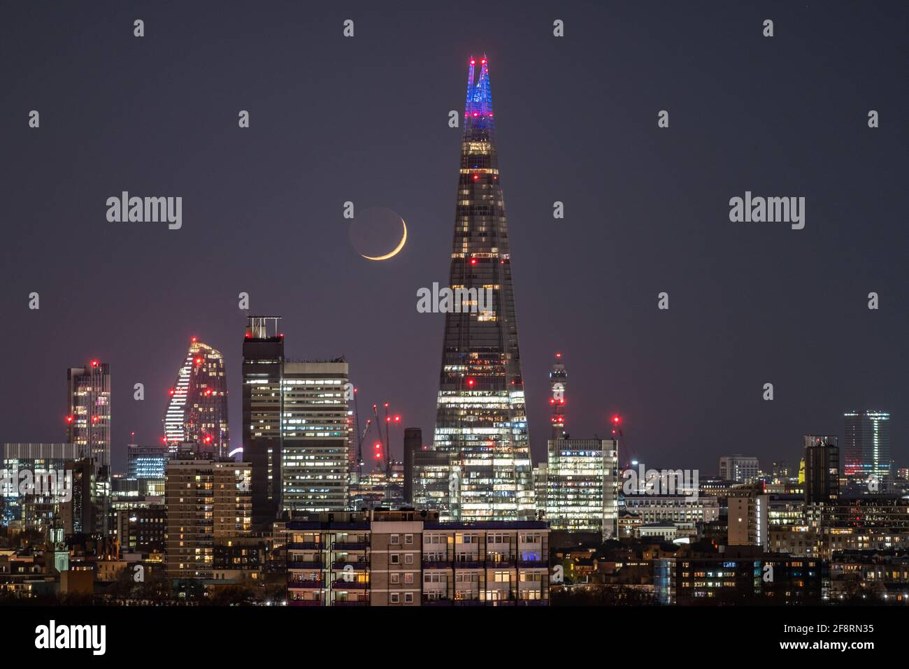 London, UK. 14th April, 2021. UK Weather: A Waxing Crescent moon sets in the late hours of Wednesday moving past The Shard skyscraper building following a north westerly direction. Credit: Guy Corbishley/Alamy Live News Stock Photo