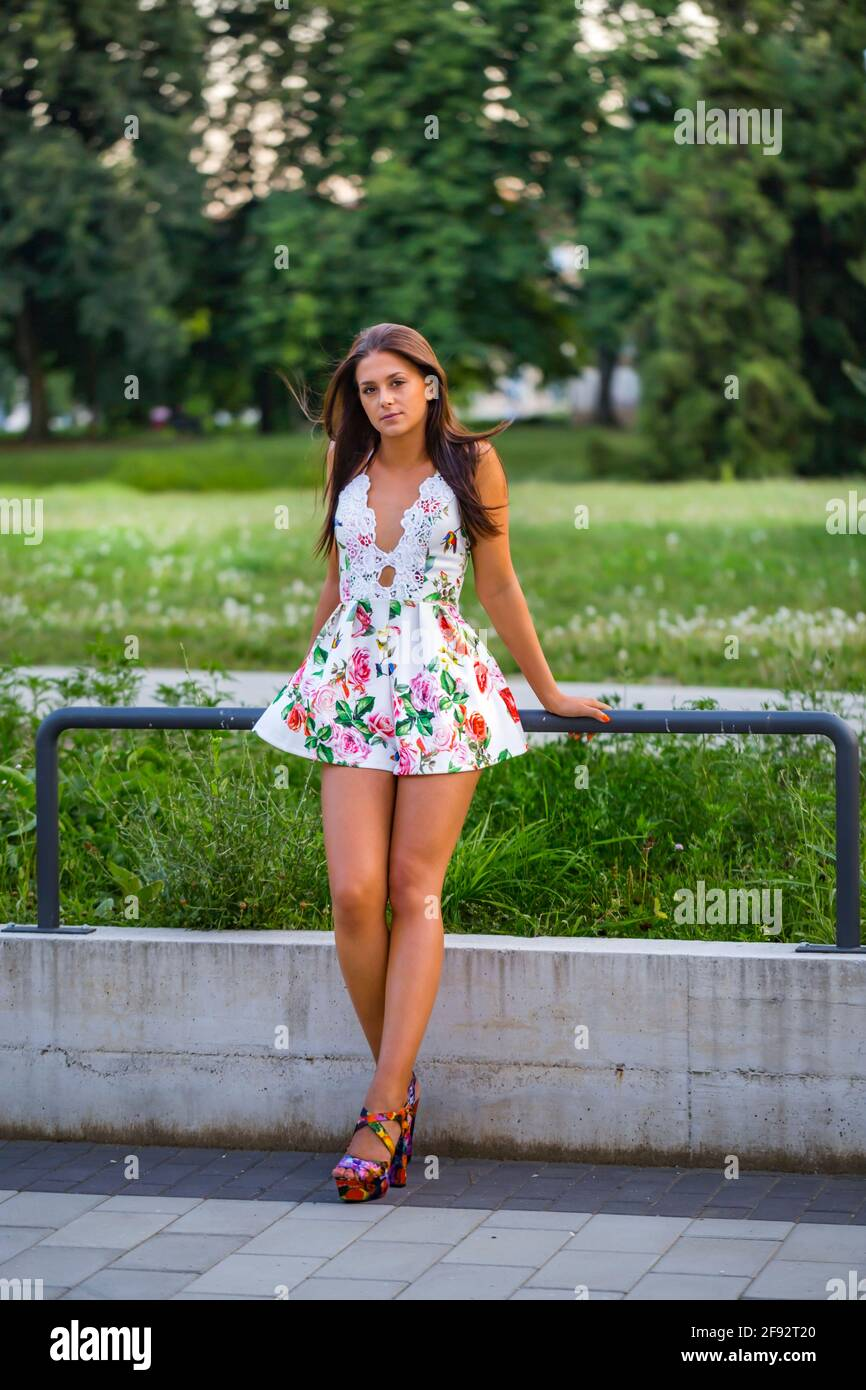 Teengirl standing isolated facing frontal view looking at camera serious eyeshot eyes eye contact wearing flowery colorful very short sundress leggy Stock Photo