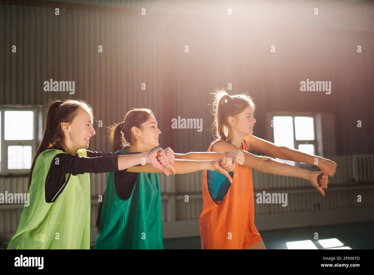 People, sporty friendship women, football fans, indoor gym, cheer up support favorite team with soccer ball showing thumbs down, sunny daylight. Stock Photo