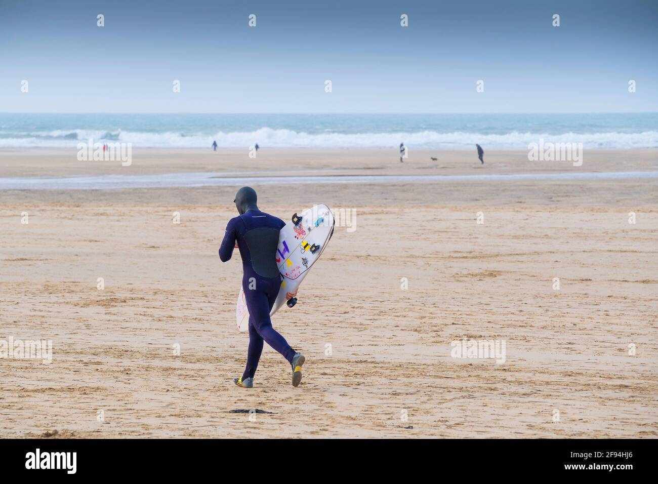 A surfer carrying his surfboard and running across Crantock Beach in Newquay in Cornwall. Stock Photo