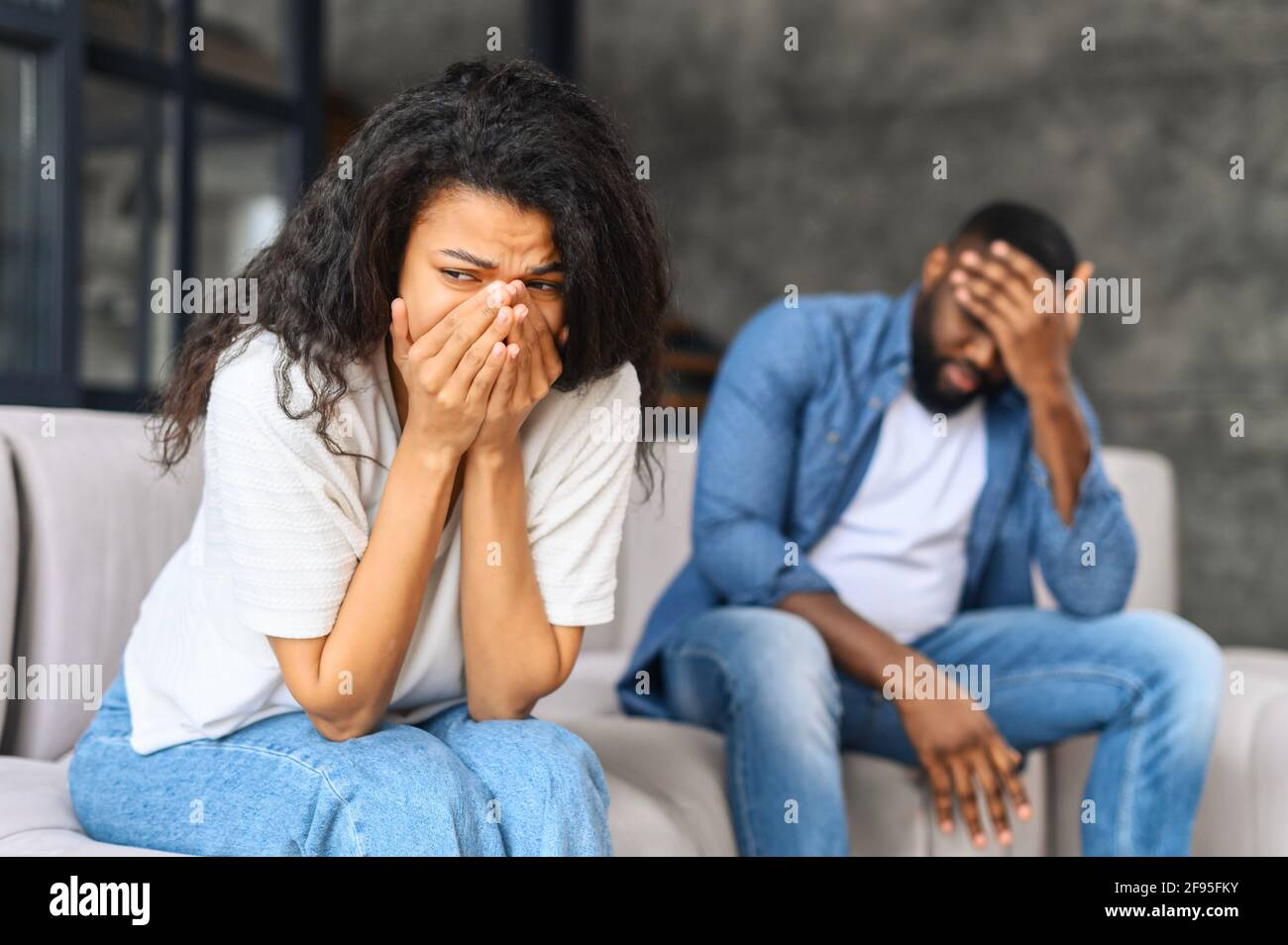 Young biracial couple relation problem concept, african woman feeling sad and crying after have an argument at home, sad or depressed woman sitting on sofa with her couple, man in defocus sits near Stock Photo