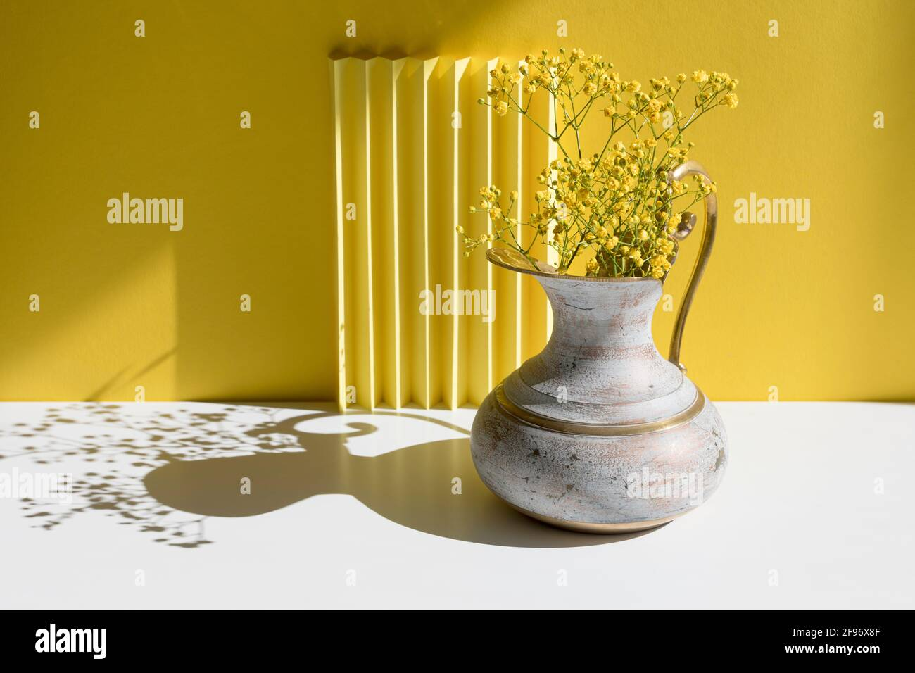 A bouquet of Gypsophila in a brass jug with harsh shadow. Minimal interior decoration concept. Minimal summer concept. Copy space. Stock Photo