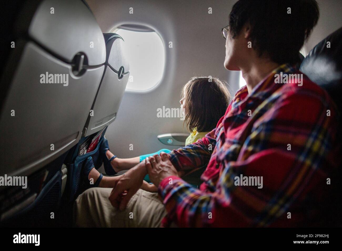 A little girl and father sit together on airplane looking out window Stock Photo