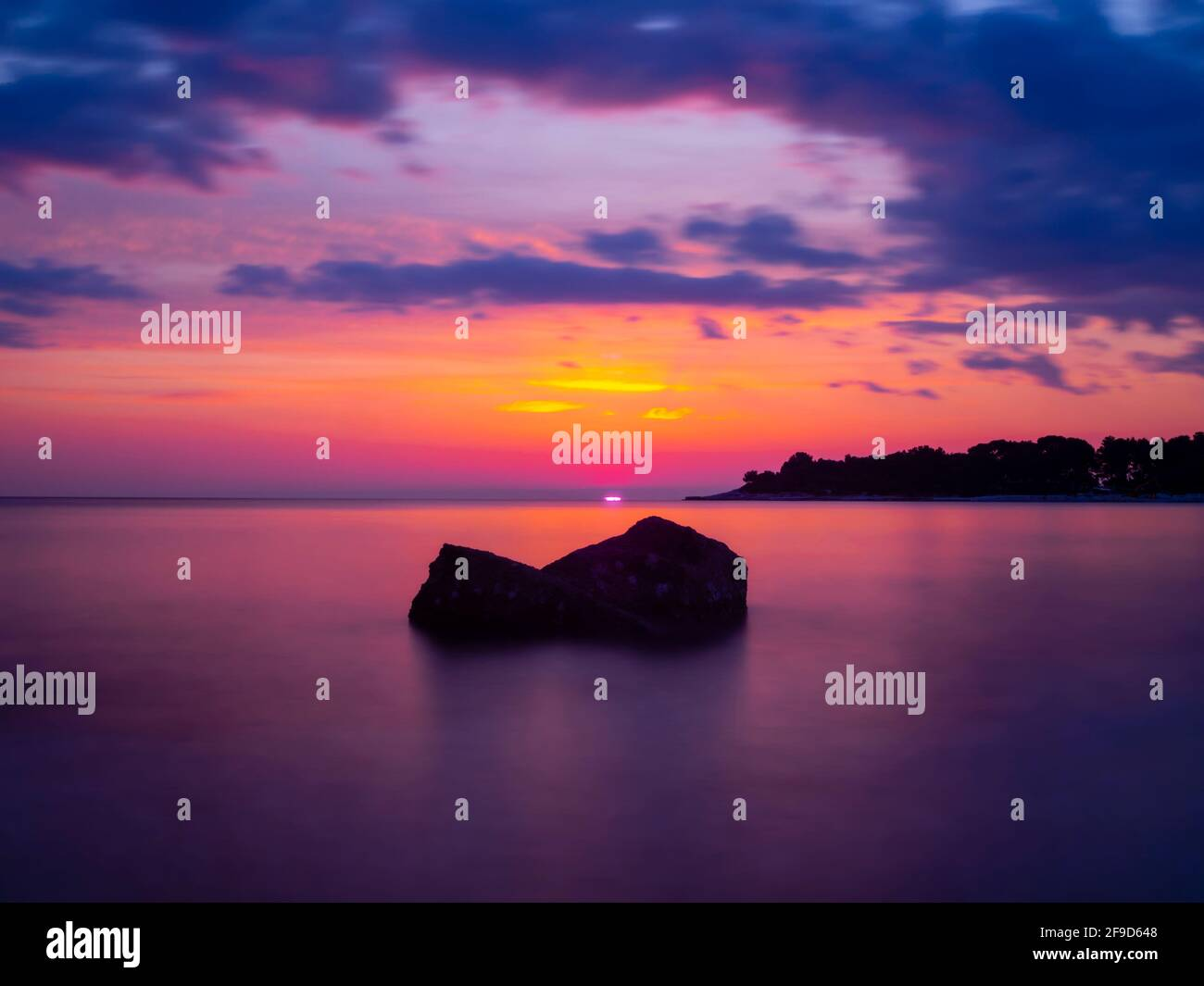 Rock boulder one single lonely loneliness alone sunset dusk gorgeous stunning idyllic pretty beautiful seaside evening tranquility Stock Photo