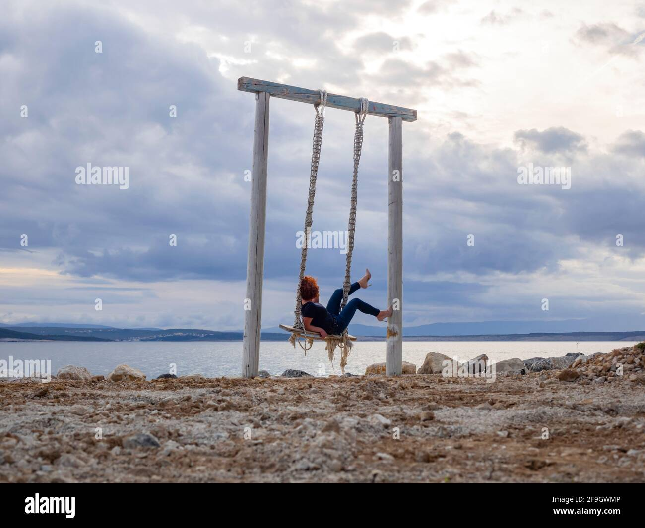 Playful woman on swings against coastline horizon raised raising legs leg upwards heels Stock Photo