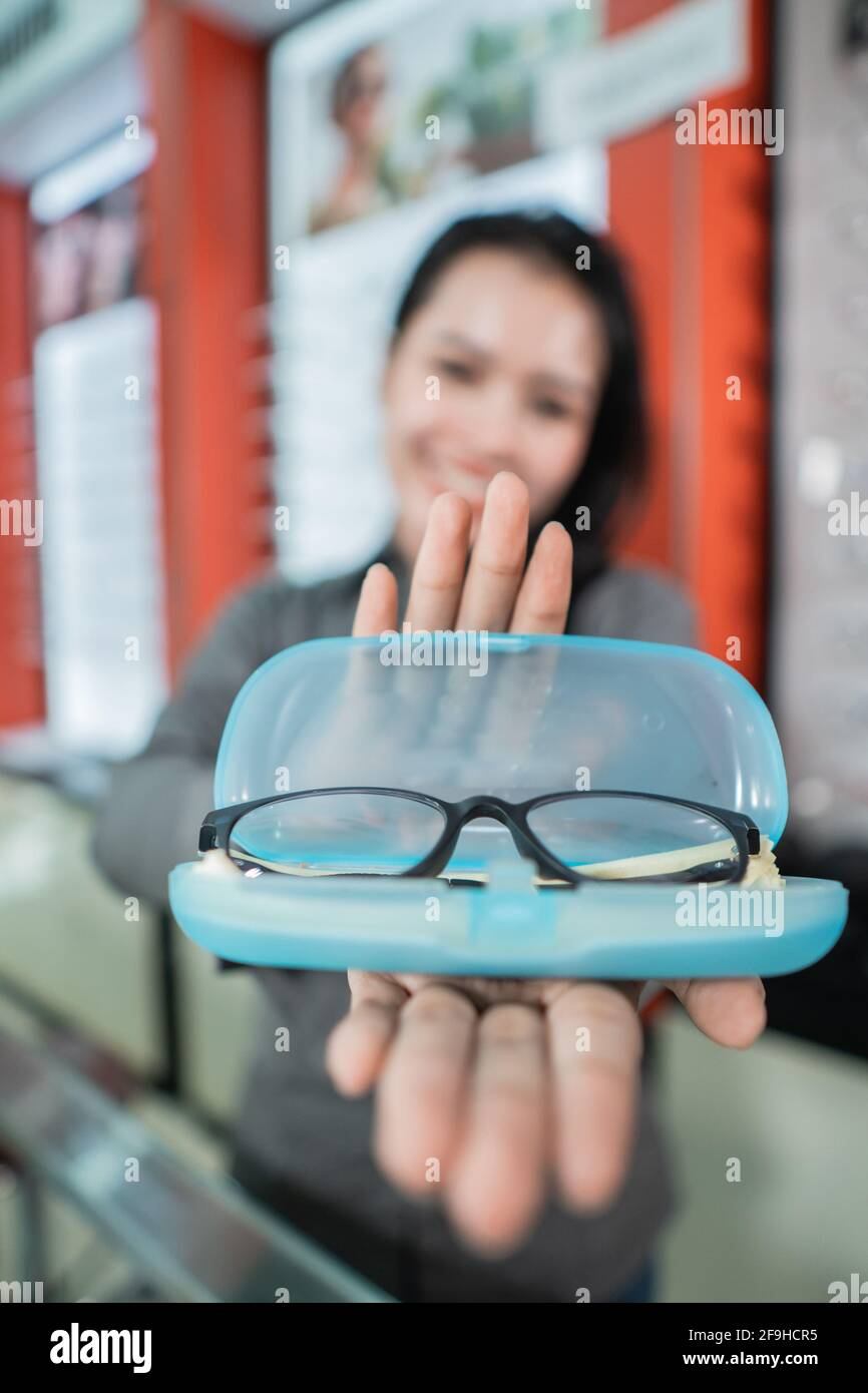 selective focus of the glasses in the eyeglass box with the background of a beautiful smiling woman Stock Photo