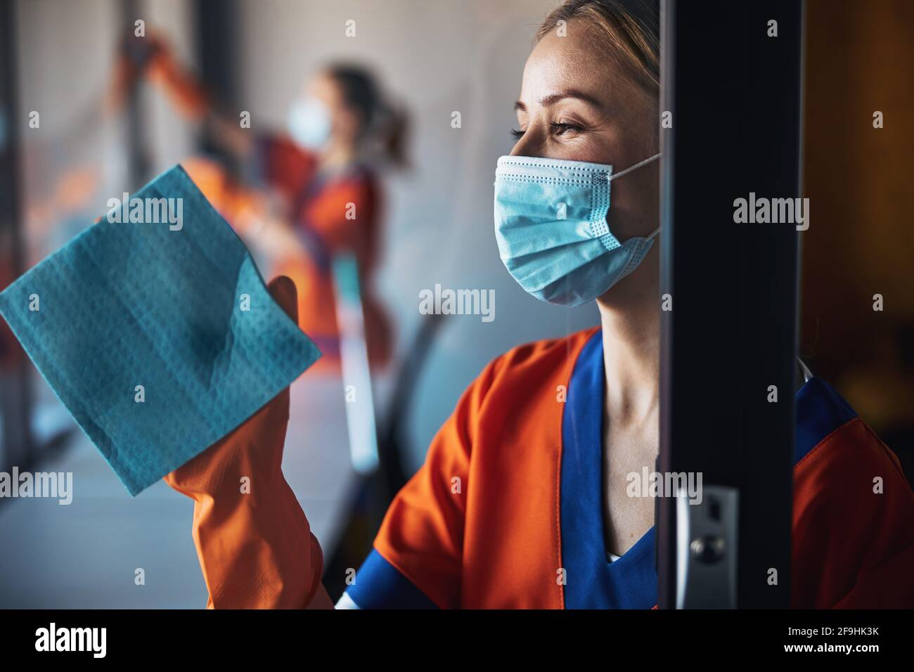 Pensive janitor in a disposable face mask doing the cleaning Stock Photo