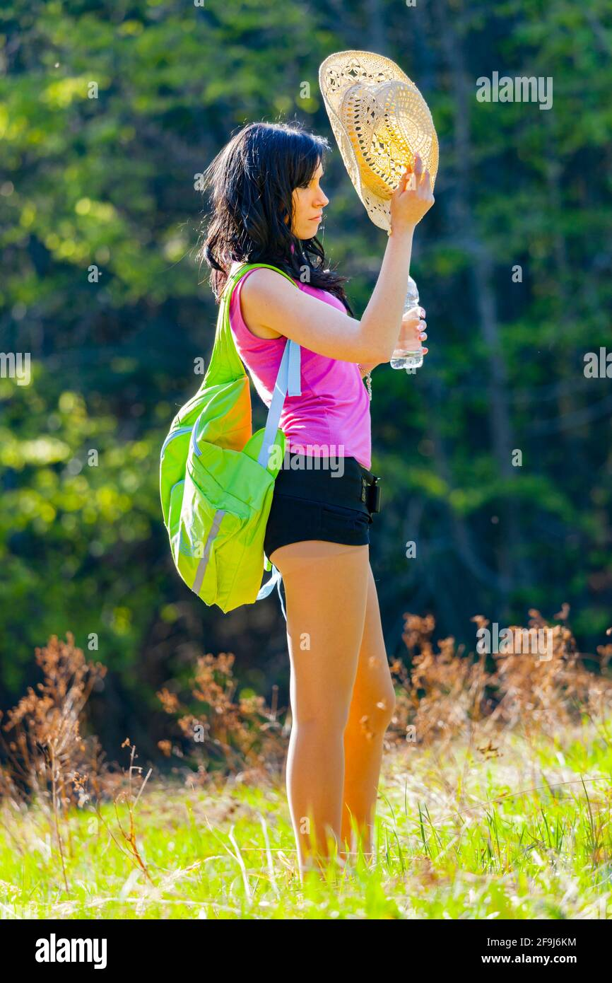 Plastic bottle water teengirl countrygirl in countryside country tired standing resting hand hold holding straw hat sideview side-view against light Stock Photo