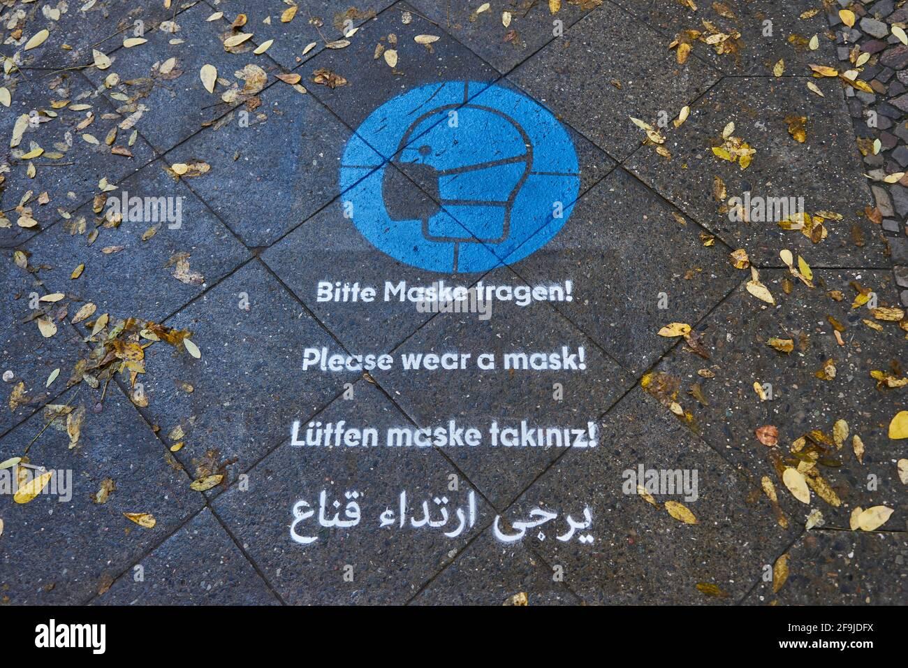 Boden-Piktogramm mit Hinweis zum Masken tragen, mehrsprachig, Infektionsschutz gegen Covid 19, Bergmannstraße, Kreuzberg, Berlin, Deutschland Stock Photo