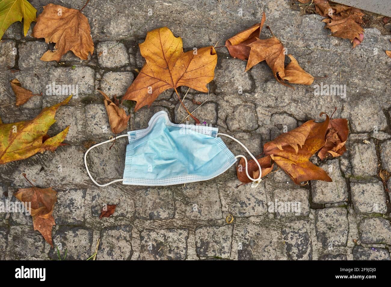 Einweg-Schutzmaske auf dem Boden neben Herbstlaub, Mund-Nase-Bedeckung, Infektionsschutz gegen Covid 19, Berlin, Deutschland Stock Photo