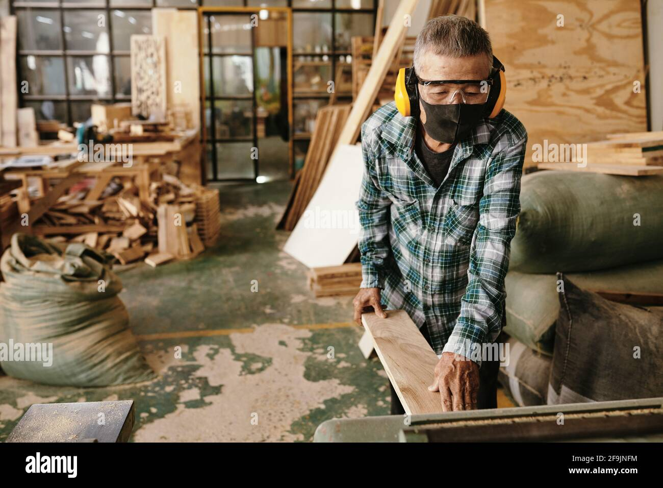 Asian carpenter in protective mask and earmuffs putting wooden board in thickness planer Stock Photo