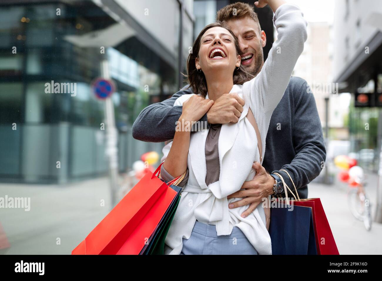 Beautiful young loving couple walking by the street with shopping bags Stock Photo